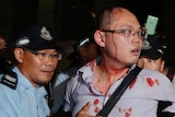 Police assist a bloodied pro-democracy protestor in Hong Kong