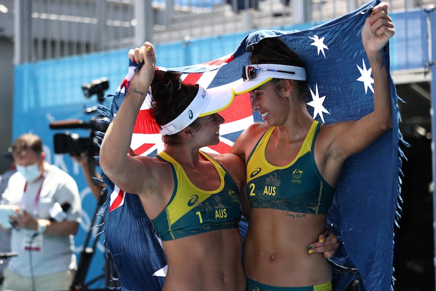 Two women wearing green and yellow bikinis hold a blue flag
