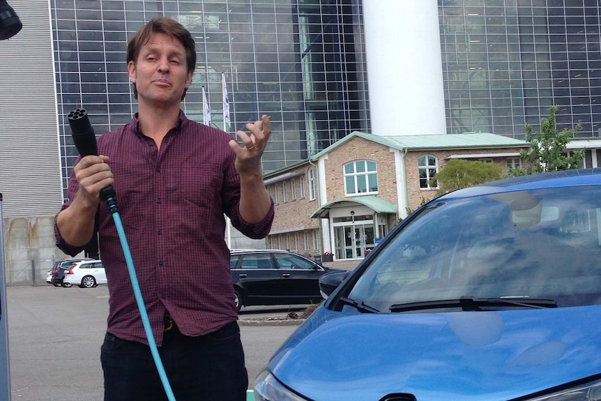 Craig Reucassel holds a large electric cable with one end plugged into a car, as he poses for the camera
