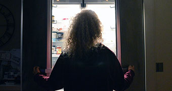 Woman looking into open fridge