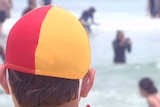 Back of a lifeguard's head looking at swimmers on Bondi Beach.