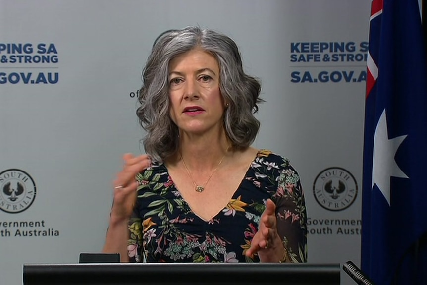 A woman with grey hair wearing a floral black top