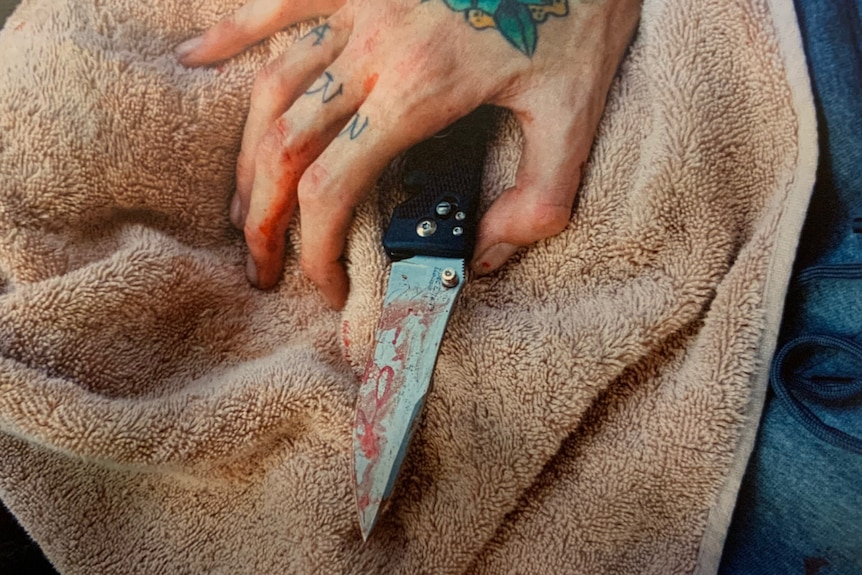 A hand with tattoos holding a bloodied knife sitting on a towel