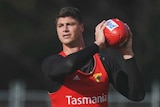 Jonathon Patton in straining gear holds an AFL football.