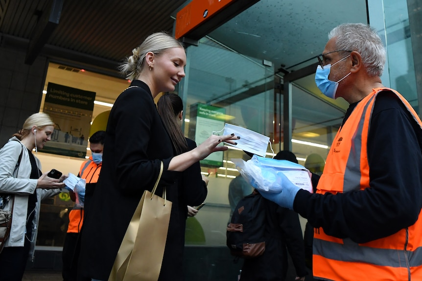 a woman reaches her hand out to get a mask from a man with  covered face