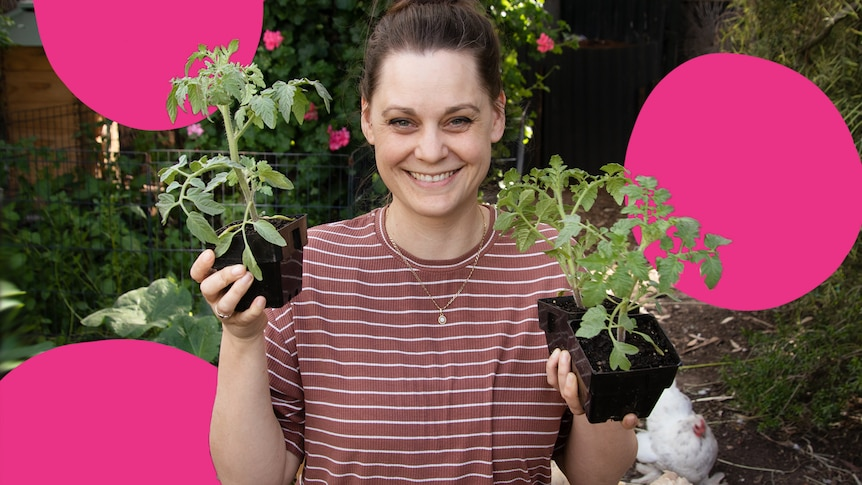 Woman holds two seedlings in pots in her Adelaide backyard.