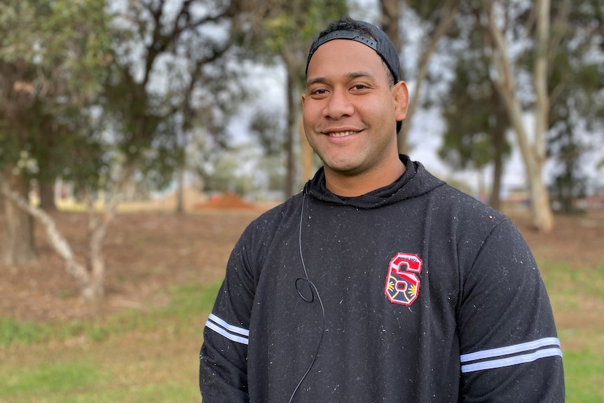 Pacific Islander man wearing a dark jumper with the number 6 on it and a cap turned backwards