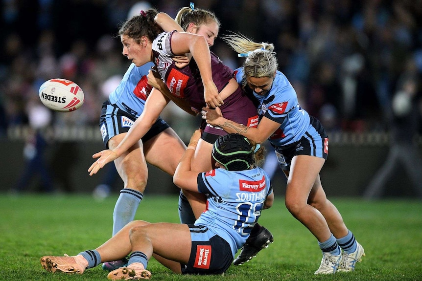A maroons player is tackled by three blues players as she passes the ball