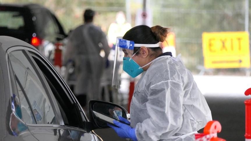 A woman in PPE talks to a driver through a car window.