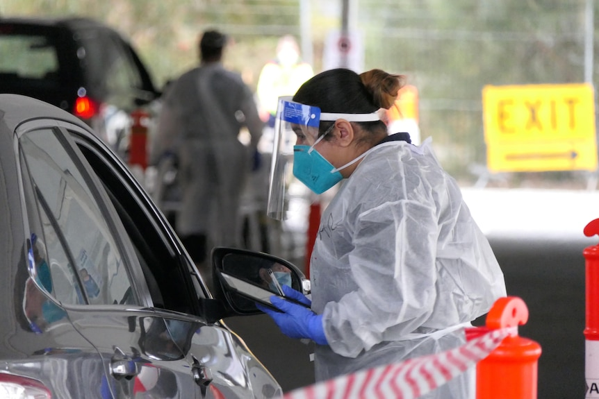 A health professional in full PPE speaks to someone at a COVID testing site.