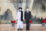 China's Foreign Minister stands next to the Afghanistan Taliban's political chief.