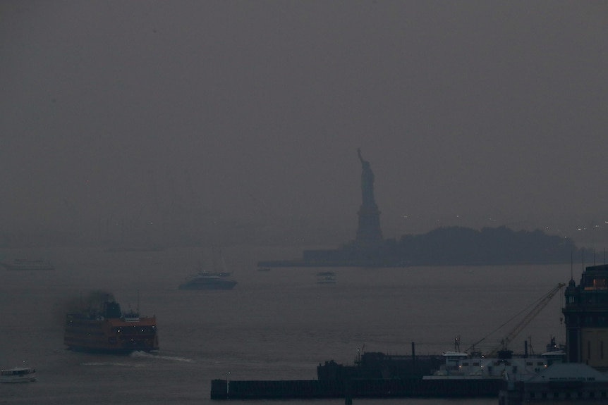 A haze of smoke settles over the Hudson river with the Statue of Liberty barely visible.