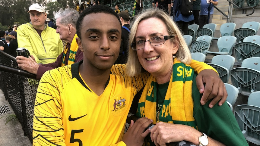 A young man in a football jersey embracing a woman.