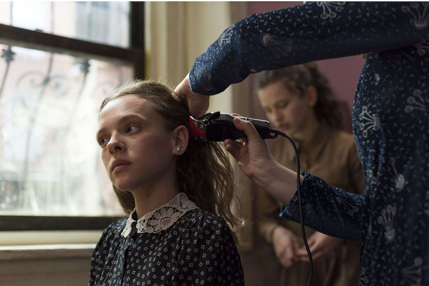 Image from the miniseries Unorthodox featuring a young Orthodox Jewish woman getting her hair shaven off