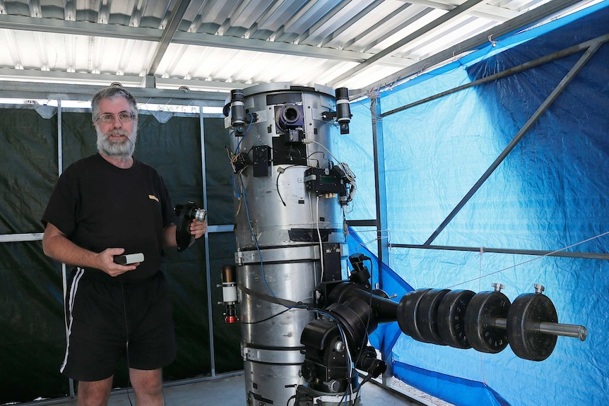 A man wearing all black and aviator sunglasses stands next to a silver telescope which is taller