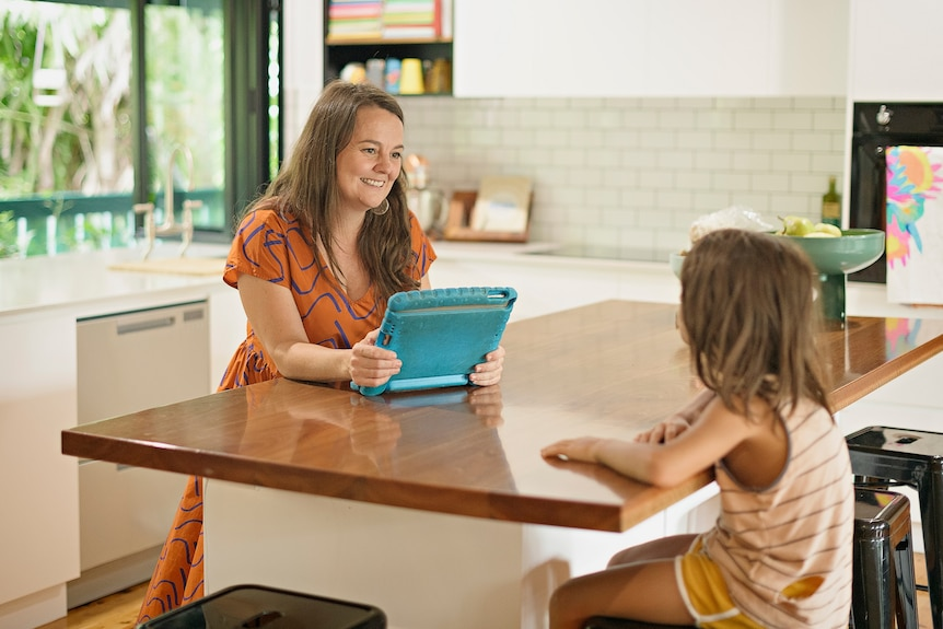 Sue Phoo holds a tablet and smiles while talking to her son in her kitchen.