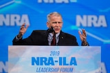 National Rifle Association President Col. Oliver North speaks at a podium in front a of bight blue NRA background