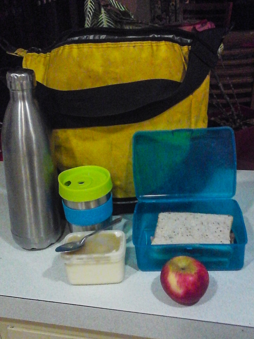 A yellow shoulder bag behind a blue sandwich box, keep cup and metal water bottle