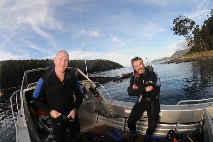 Photograph of two men in wetsuits in a boat.