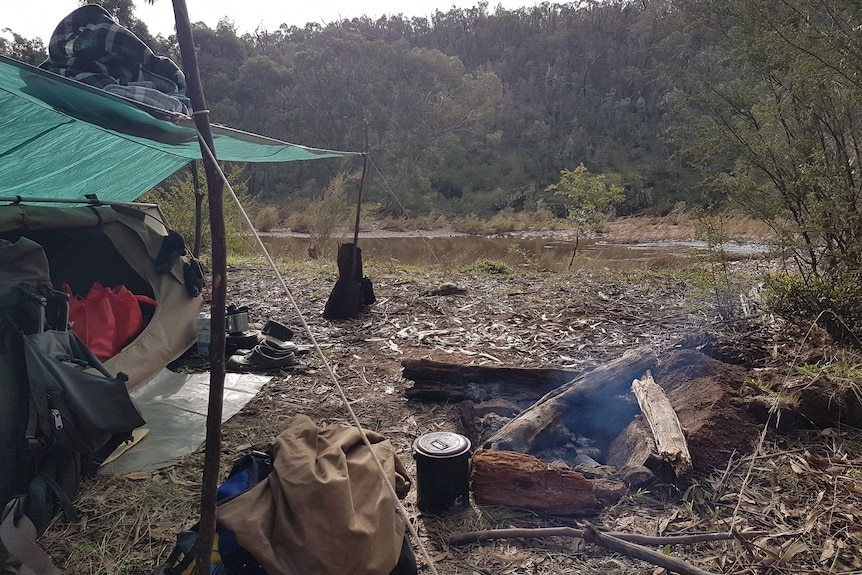 A camp site in Licola. Billy and swag in foreground, with river in the background