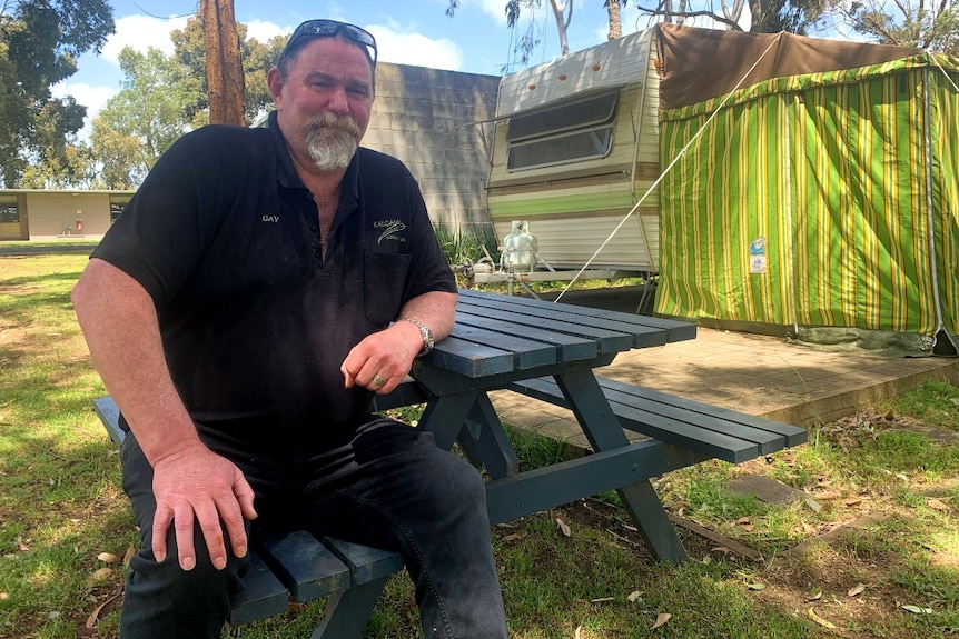 Man sits on bench at a caravan park