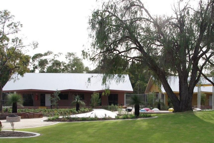 A view of Bennett Brook Disability Justice Centre with trees and lawn in the foreground.