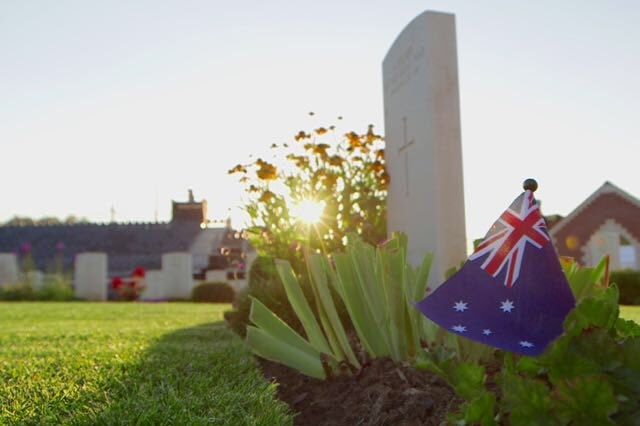 The sun rises behind a grave with an Australian flag in Fromelles.