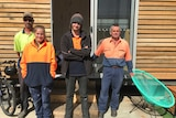 A team of volunteers stand outside a shipping container they converted to a tiny house.