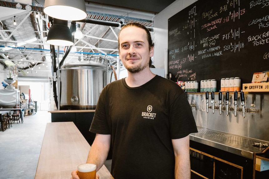 A man in a black t-shirt stands behind a bar holding a beer.