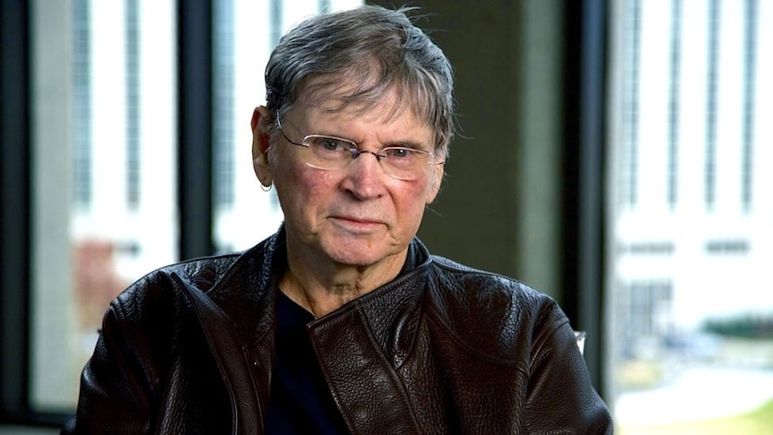 An elderly man with grey hair, glasses and a black leather jacket looks at camera in sunlit room.