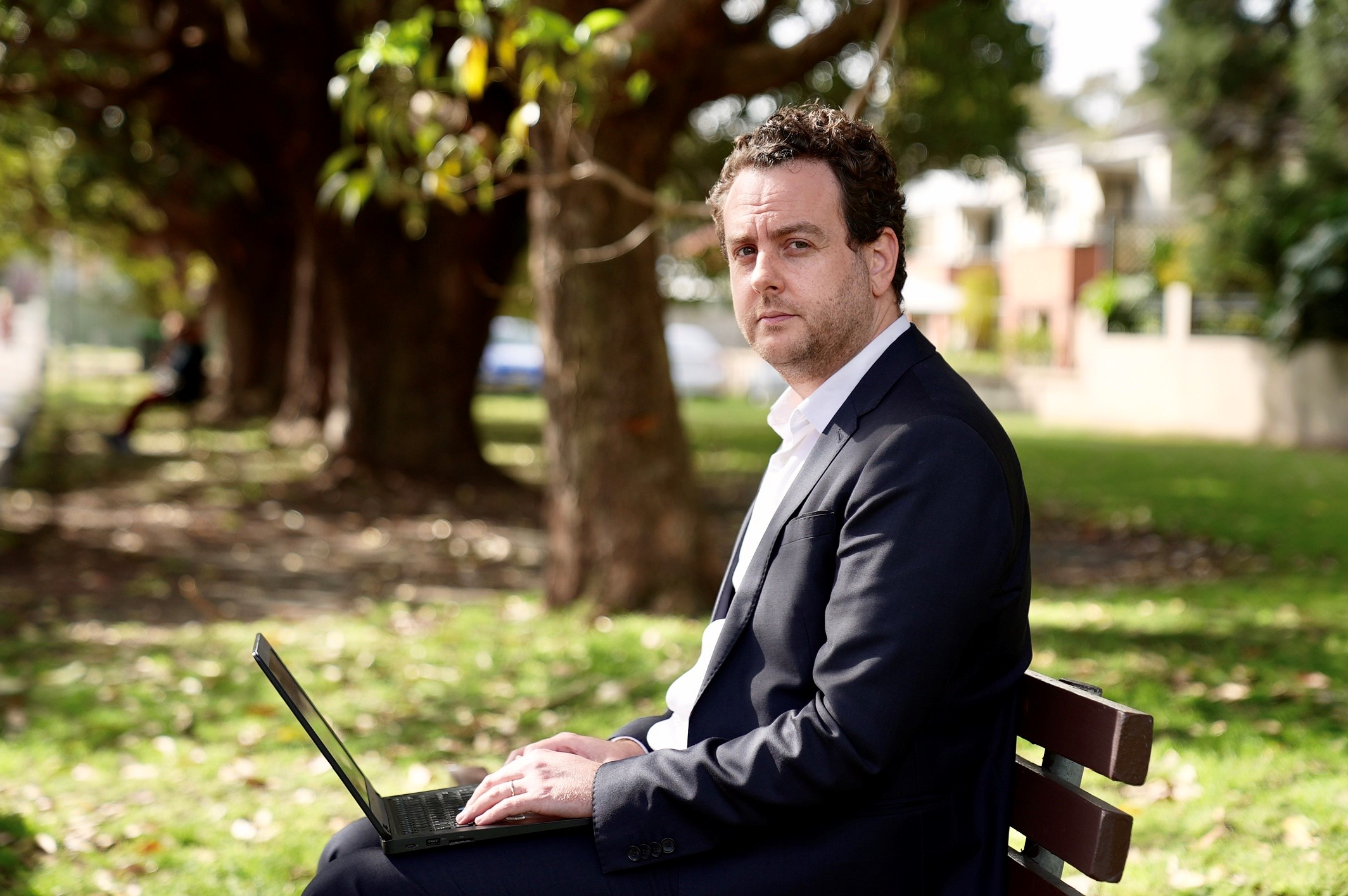 Xavier in a black suit sits at a park bench in Marrickville.