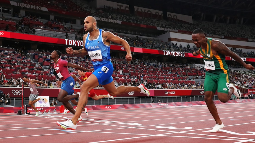 Lamont Jacobs clenches his fist as he crosses the finish line in the 100m Tokyo Olympics final.