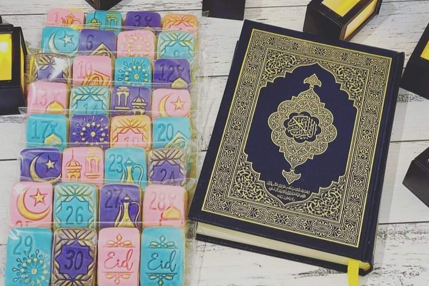 A box of colorful cakes next to the Koran.