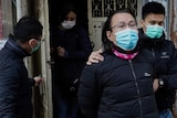 Daniel Wong Kwok-tung wearing a face mask is lead away by police as he looks at the camera