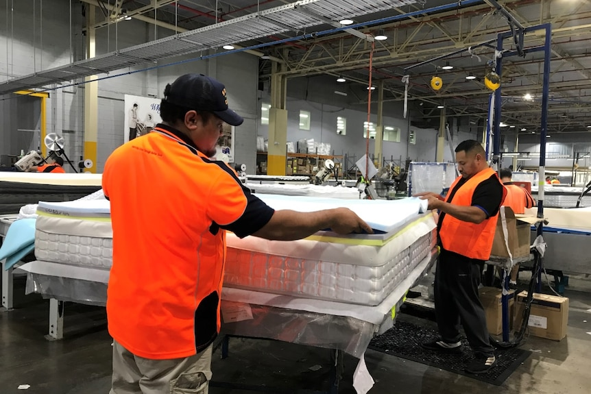 Two workers building a mattress at a factory, wearing orange, high visibility vests.