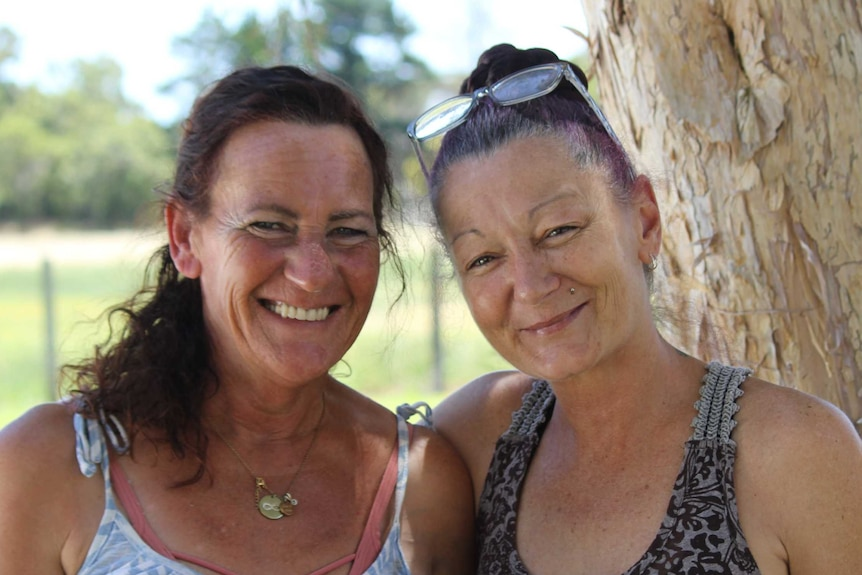 Two women, one has a arm around the other's shoulder, standing outside under a tree on a hot sunny day and smiling.