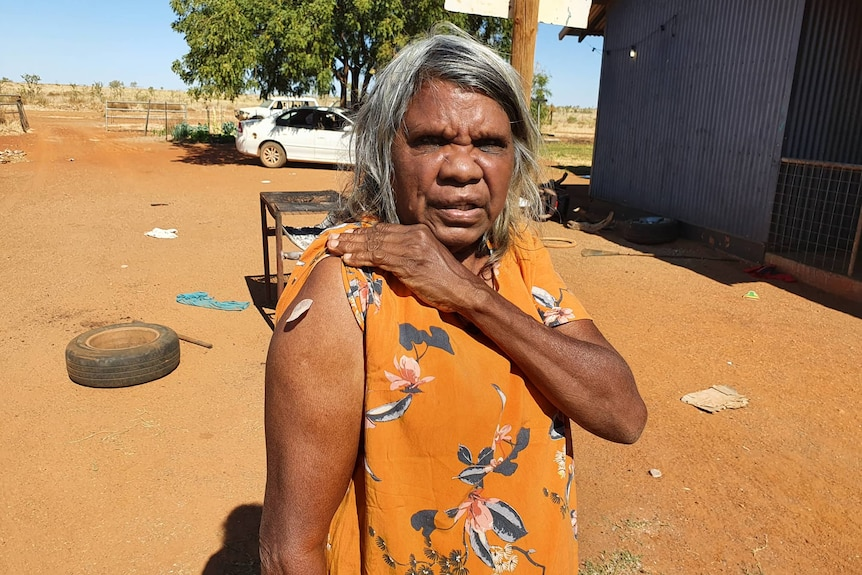 An Aboriginal woman holds her sleeve up, showing where she had received her COVID-19 vaccine.