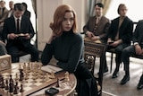 A woman with orange hair wearing a black high neck sweater sitting at a table with chess board and chess pieces