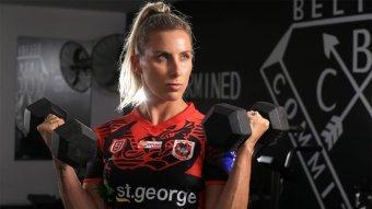 St George Illawarra Dragons fullback Sam Bremner holds two dumbbells up to her shoulders.
