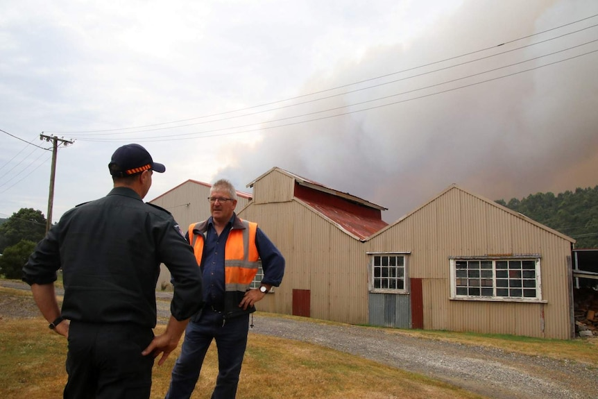 Phil Vickers stands in front of a shed-like structure, there's a smoke plume in the background.