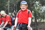 Boy in school hat smiling enthusiastically