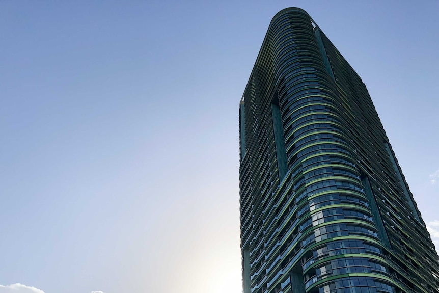 A blue and green high-rise building is seen to the right of frame with clear blue skies surrounding the skyscraper.