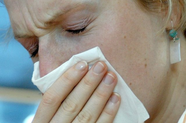 A woman sneezes into a tissue