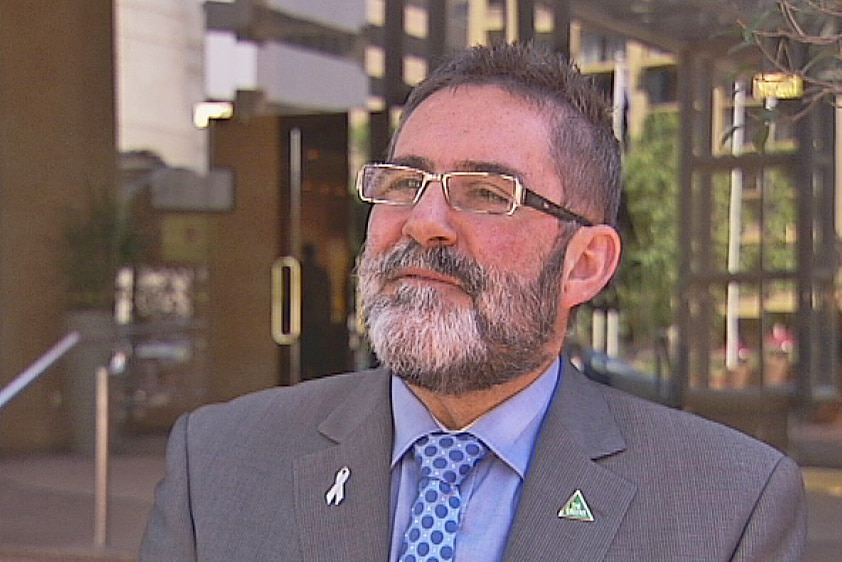 A white man wearing a suit and glasses. His hair and beard are black and grey