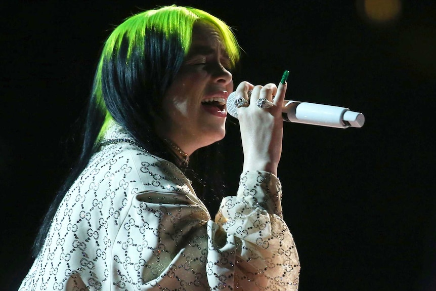 A woman with green hair sings in darkness on stage