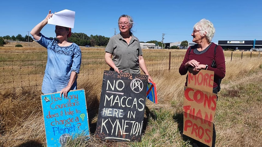Three residents stand in front of a vacant paddock holding signs saying 'No Maccas here in Kyneton', 'More Cons than pros'.