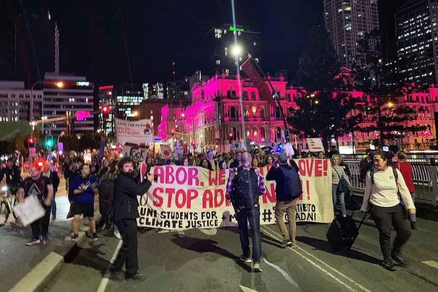 Hundreds of anti-Adani protesters march over Victoria Bridge towards the ABC at South Bank.