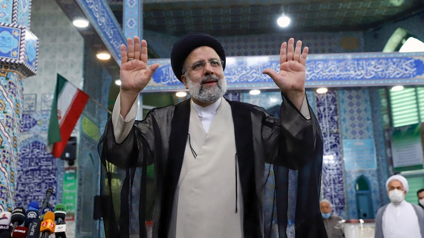Hardliner Ebrahim Raisi gestures with arms up and palms outward after voting during the election on June 18.