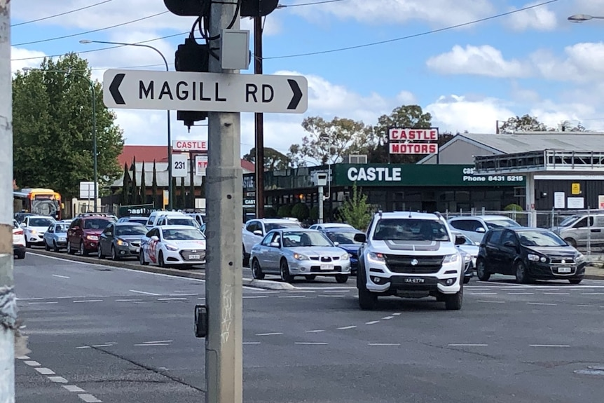 Signage for Magill Road with traffic driving across the intersection in the background
