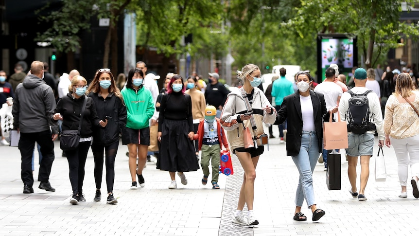 Shoppers wearing masks on a busy stre